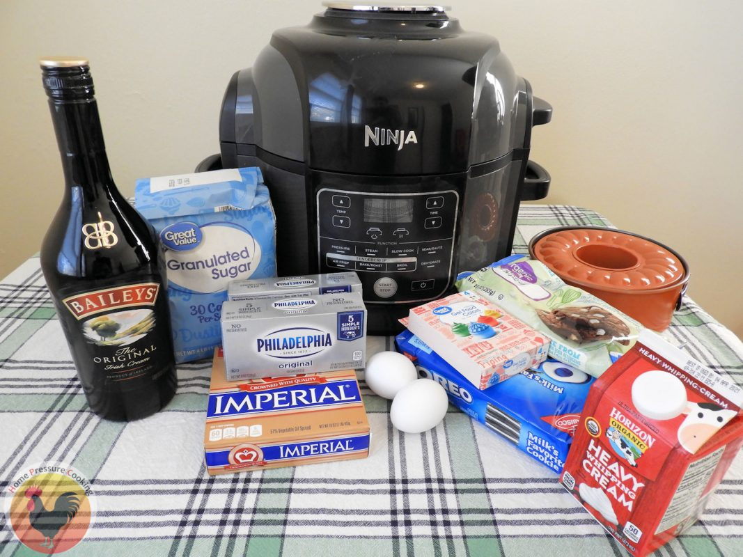 The ingredients required to make the Bailey's Instant Pot Cheesecake sitting in front of a Ninja Foodi. They include granulated sugar, butter, two eggs, gel food colors, white chocolate chips, oreos, heavy whipping cream and Bailey's Irish Cream.