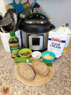 A picture of all the ingredients needed for making Baked Potatoes in the Instant Pot. This includes the potatoes, some chives, a cup of shredded cheese, a cup of bacon bits, a cup of salt and pepper, some sour cream, and a bottle of extra virgin olive oil. Also pictures are a small cutting board and a 6 Qt. Instant Pot Duo Nova.