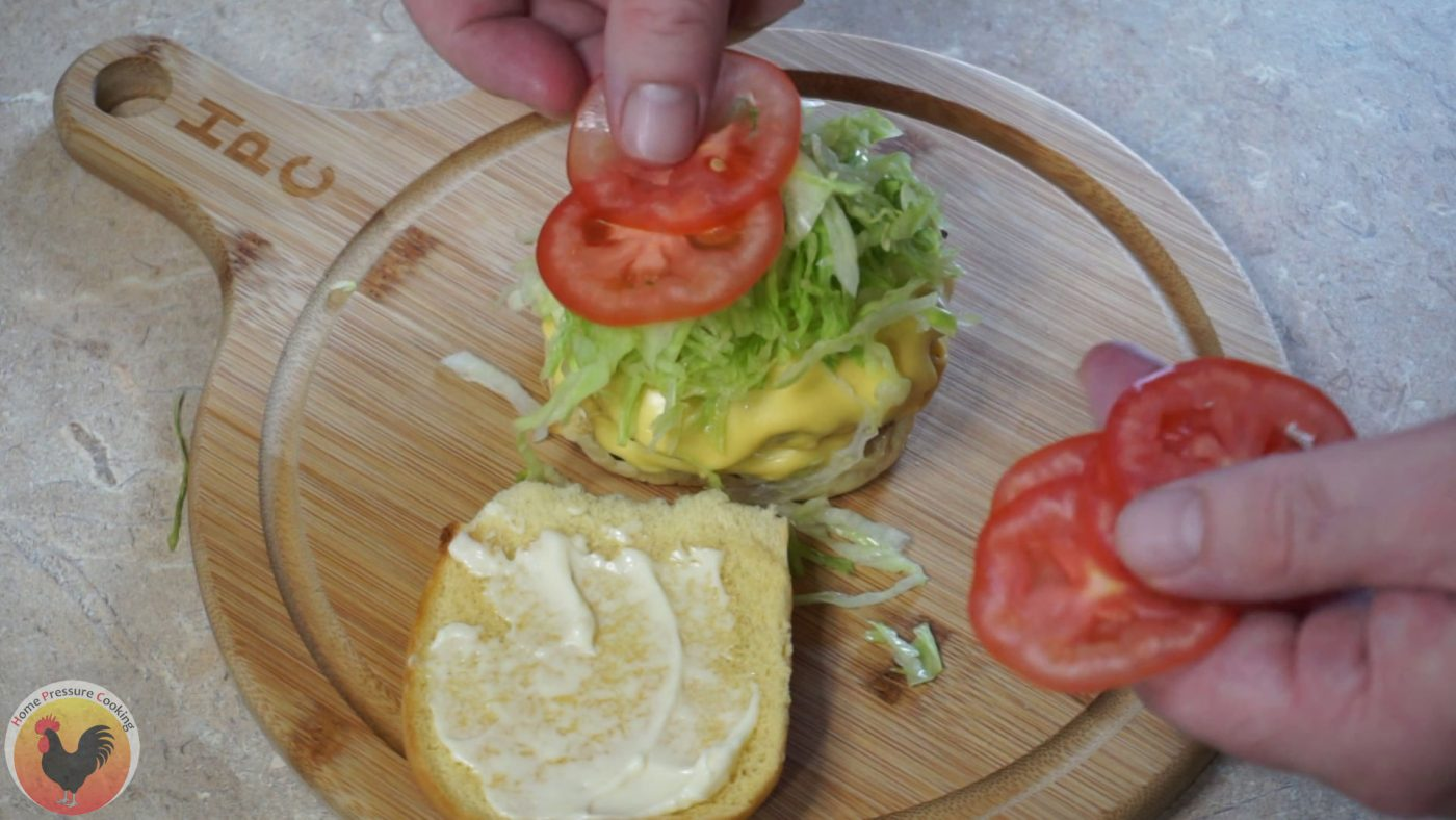A freshly grilled blt burger being topped with lettuce and tomato.