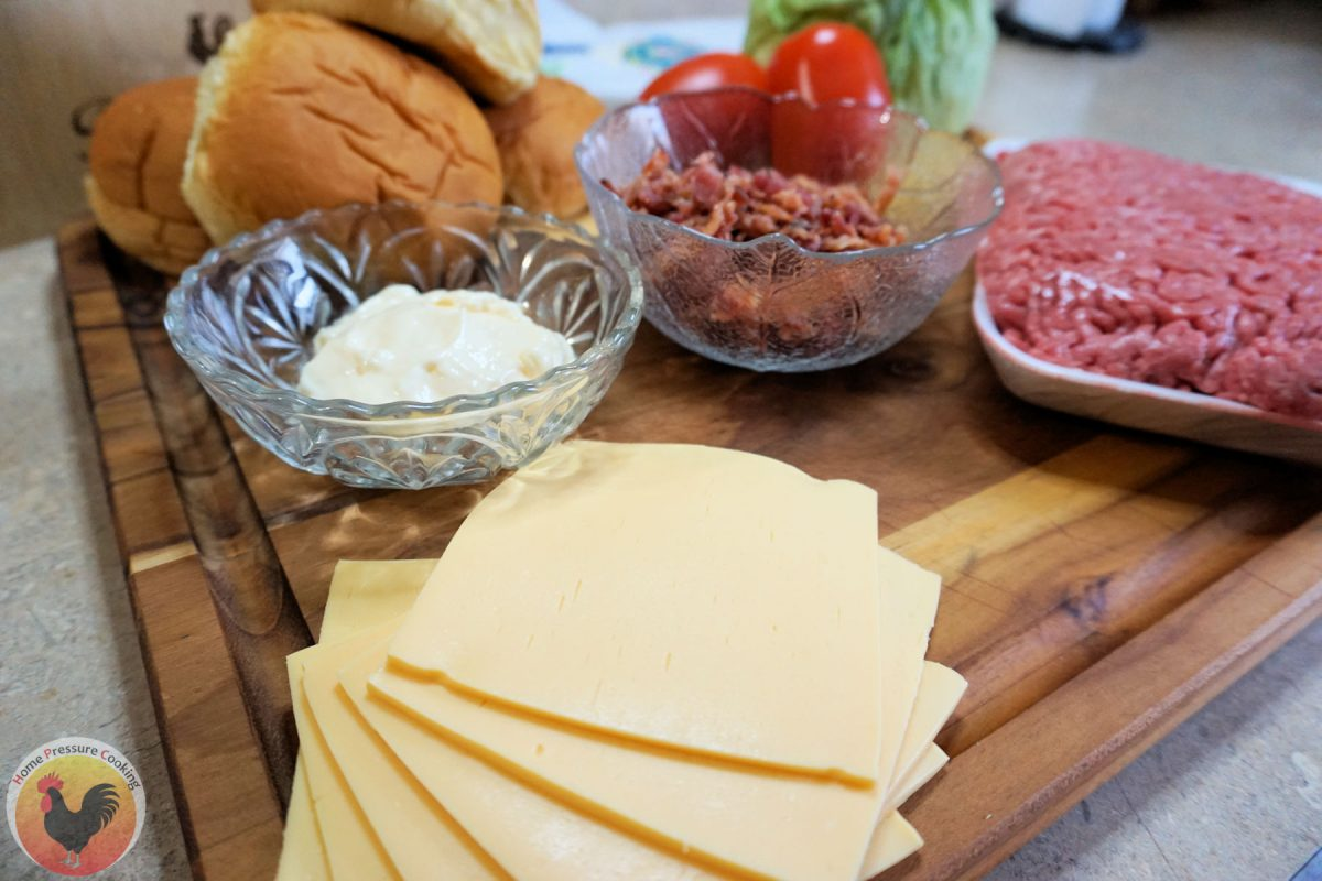 A picture of ingredients needed for the blt burger recipe including raw ground chuck, bacon bits, tomatoes, lettuce, cheese and potato rolls.
