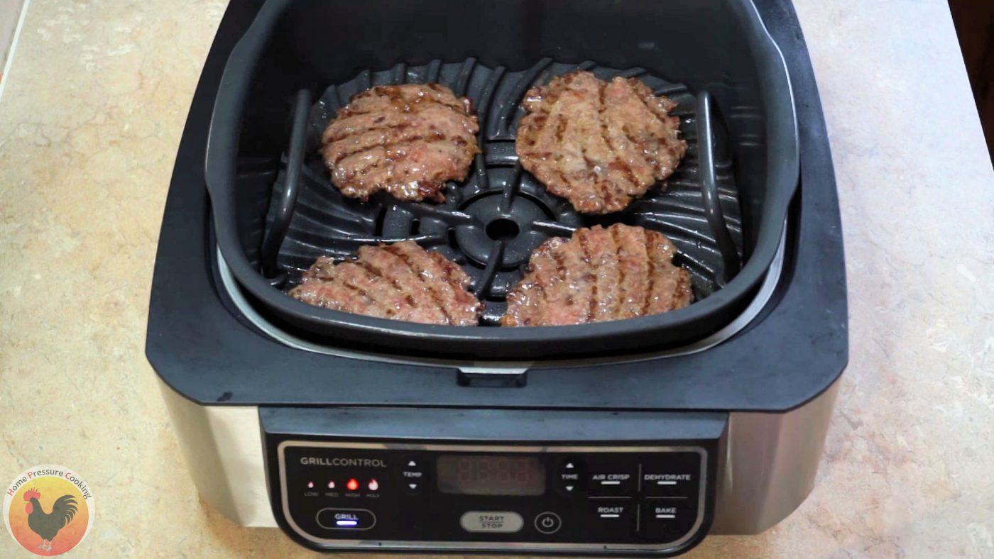 Four ground chuck beef patties being cooked in the Ninja Foodi Grill.