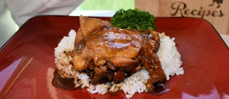 A focused image of some hoisin chicken resting on a bed of white rice.