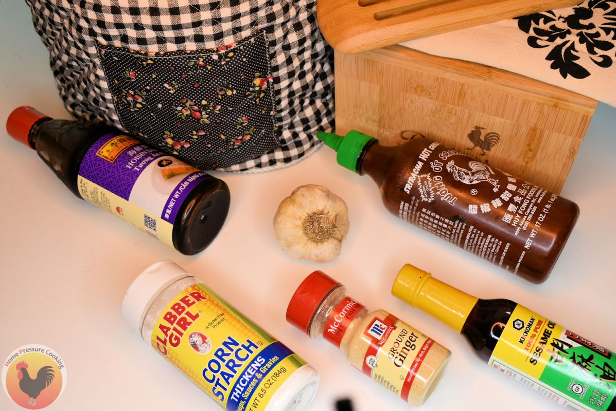 Various bottles of sauces and spices used with the hoisin chicken recipe including hoisin sauce, sriracha sauce, corn starch, ground ginger, sesame oil, and some garlic.