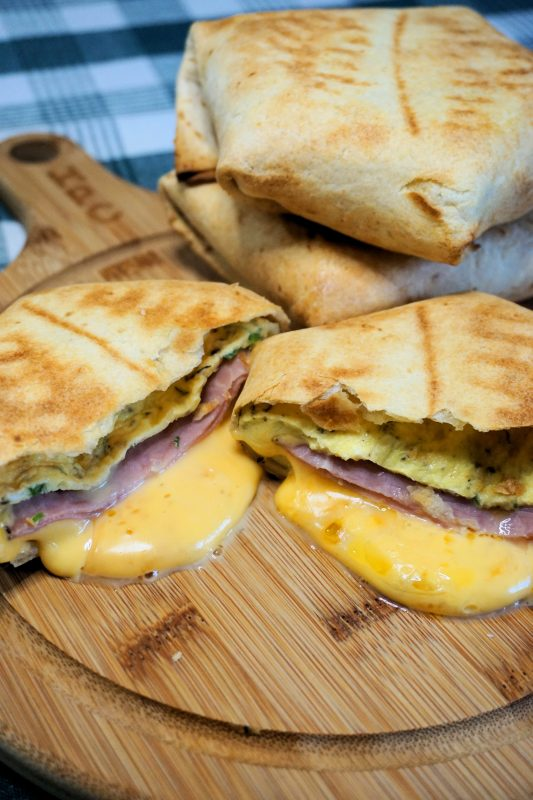 a close up of breakfast crunchwraps with melted cheese dripping out of the sliced side sitting on a cutting board