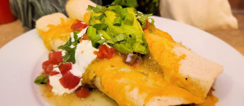 close up cropped shot of beef enchiladas used for the banner on the top of the site page.