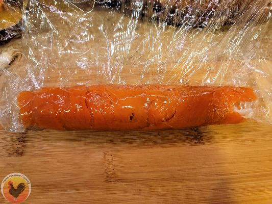 photo showing a single layer of plastic wrap over the rolled sushi, ready to be cut