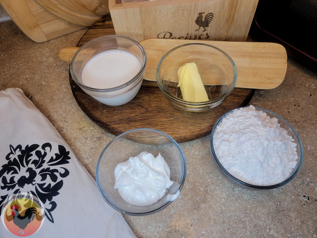 shows 4 bowls containing the ingredients, biscuit mix, sour cream, milk, and butter. Also pictured is a spurtle, printed bag for storage and a recipe box.