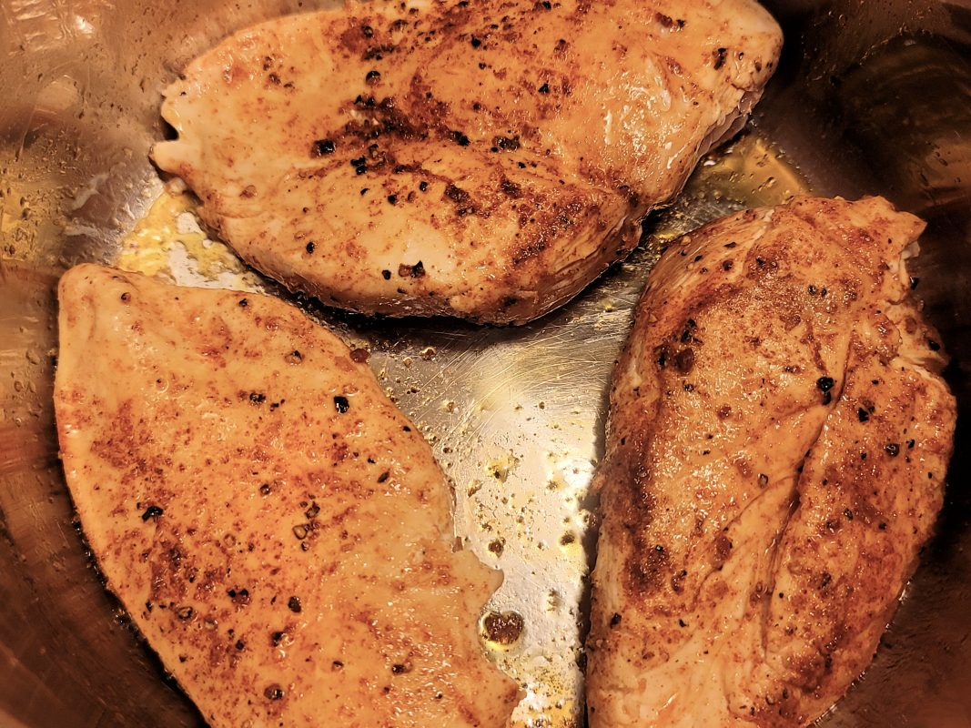 chicken being browned in the bottom of the pressure cooker using the saute setting
