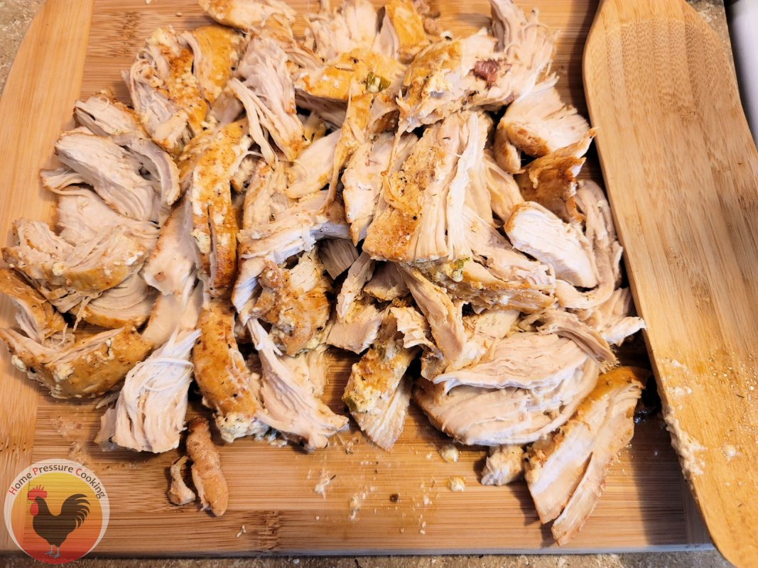 Shows the chicken pulled apart but not quite shredded on a cutting board, ready to be added back to the pressure cooker